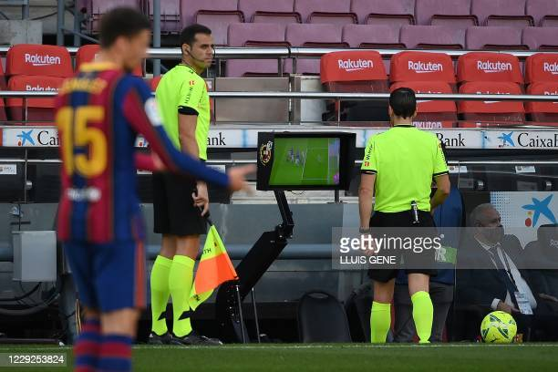 Spanish referee Juan Martinez Munuera reviews the VAR for a penalty check during the Spanish League football match between Barcelona and Real Madrid...