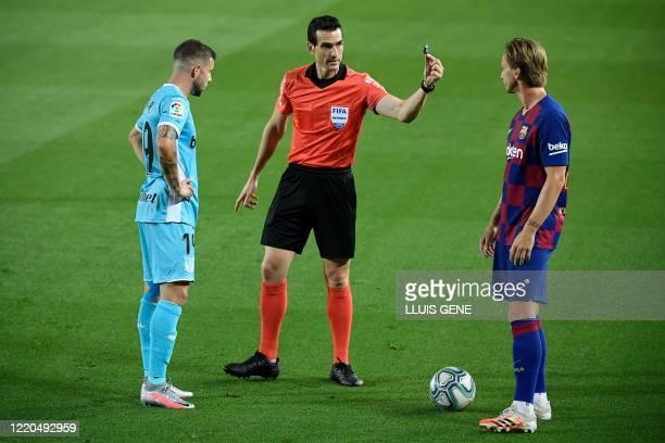 Spanish referee Juan Martínez Munuera speak to Barcelona's Croatian midfielder Ivan Rakitic during the Spanish league football match FC Barcelona...