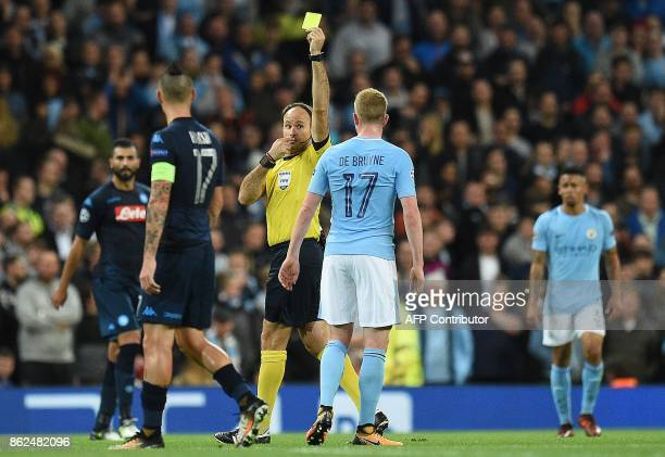Spanish referee Mateu Lahoz shows a yellow card to Manchester City's Belgian midfielder Kevin De Bruyne during the UEFA Champions League Group F...