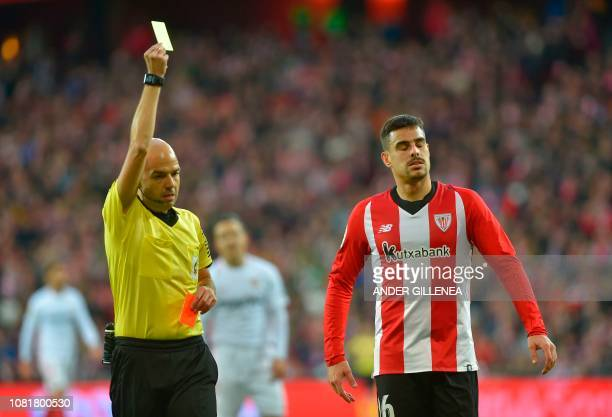 Spanish referee Pablo Gonzalez Fuertes shows a yellow card to Athletic Bilbao's Spanish midfielder Dani Garcia during the Spanish League football...