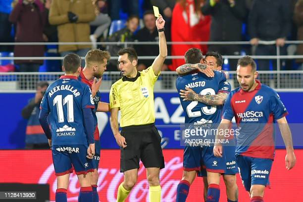 Spanish referee Ricardo De Burgos Bengoetxea shows a yellow card to SD Huesca's Argentinian forward Chimy Avila as he celebrates with teammates after...