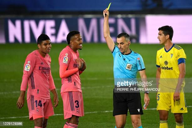 Spanish referee Santiago Jaime Latre presents a yellow card to Real Madrid's Brazilian defender Eder Militao during the Spanish League football match...
