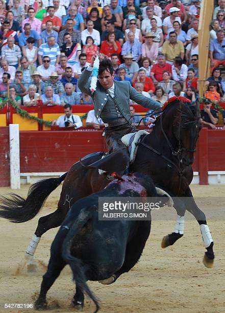 Spanish rejoneador Manuel Manzanares brandishes a banderilla above a bull during the San Juan Feria at Alicante bullring on June 24 2016 / AFP /...