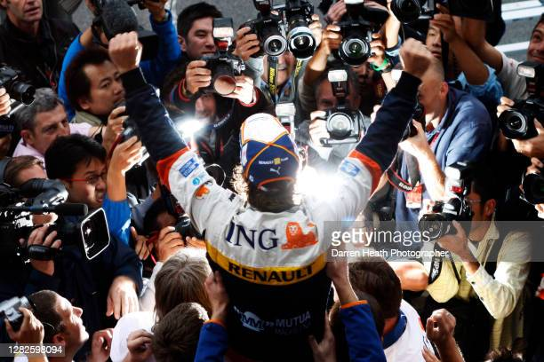 Spanish Renault Formula One driver Fernando Alonso is held aloft by his Renault mechanics in celebration of winning the 2008 Japanese Grand Prix at...