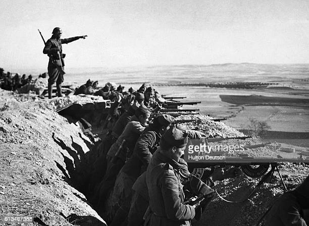 Spanish Republicans fighting against General Franco's fascist forces line up in a trench guns ready for an attack during the Spanish Civil War Spain...