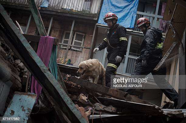 Spanish rescue workers with a rescue dog look for survivors among debris following an earthquake in the Nepalese capital Kathmandu on April 28 2015...