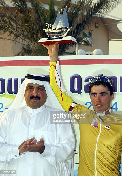 Spanish Rider Francisco Ventoso holds the trophy as he poses next to Sheikh Khaled bin Ali al-Thani, the head of Qatar's cycling federation, after...