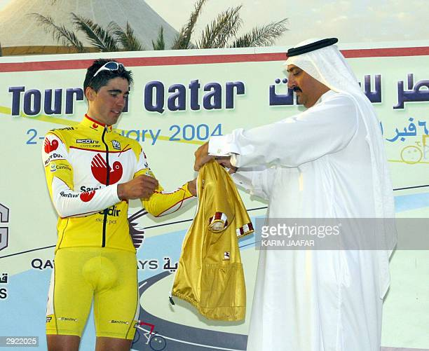 Spanish Rider Francisco Ventoso receives the golden shirt from Sheikh Khaled bin Ali al-Thani, the head of Qatar's cycling federation, after winning...
