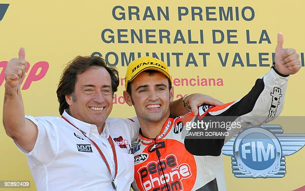 Spanish rider Hector Barbera celebrates on the podium with Sito Pons after winning the 250cc race of the Valencia motorcycling Grand Prix at the...