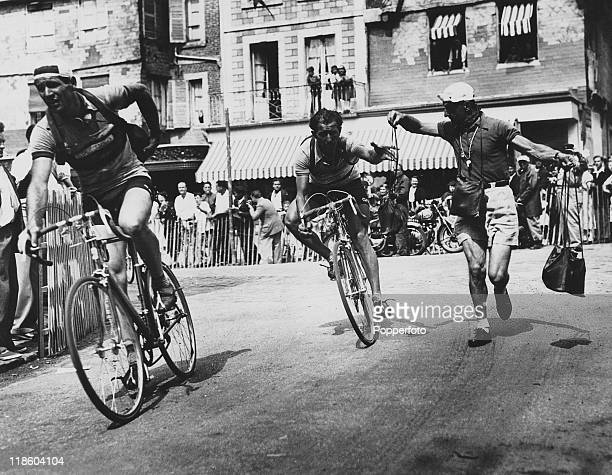Spanish road racer Dalmacio Langarica picks up his lunch during the Tour de France 1952