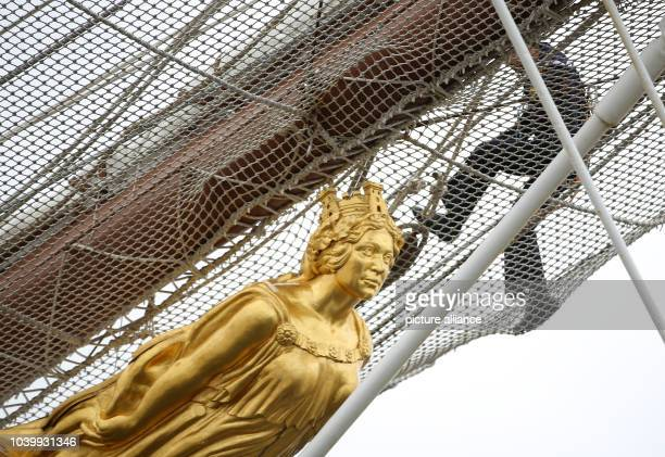 A Spanish sailor moves across the bow netting above the figurehead on training ship Juan Sebastian de Elcano of the Spanish navy in Hamburg Germany...