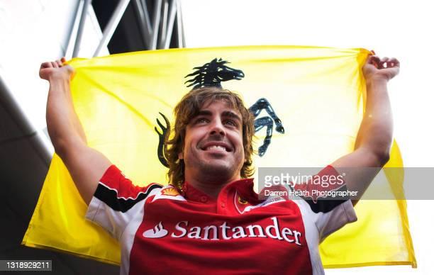 Spanish Scuderia Ferrari Formula One driver Fernando Alonso smiles while holding aloft a Ferrari flag in celebration of winning the 2011 British...