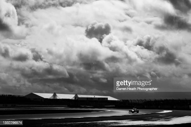 Spanish Scuderia Ferrari Formula One team racing driver Fernando Alonso driving his F2012 racing car through Club Corner under a dramatic cloudscape...