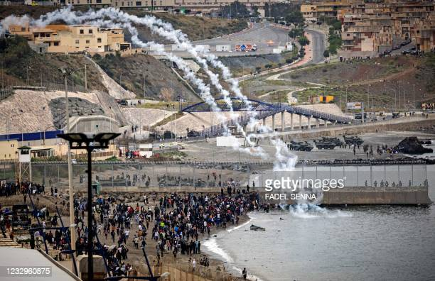 Spanish security forces launch tear gas canisters across a border fence as Moroccan migrants rally in the northern town of Fnideq to attempt crossing...