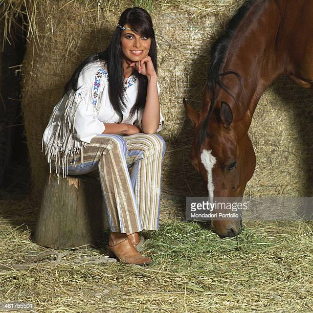Spanish showgirl Natalia Estrada posing with a horse in the stables MHR of Cassano d'Adda Italy on May 24th 2004