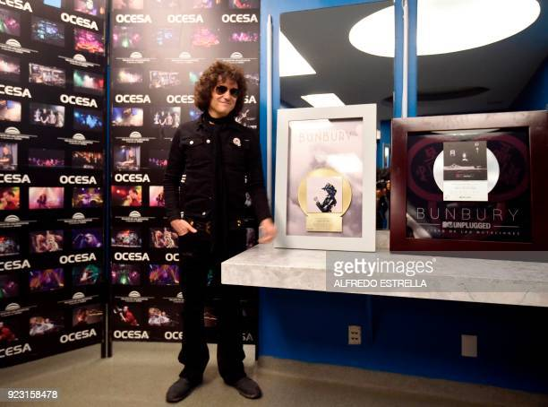 Spanish singer and composer Enrique Bunbury poses with his 'El Libro de las Mutaciones' platinum album and his 'Expectativas' gold album at the...