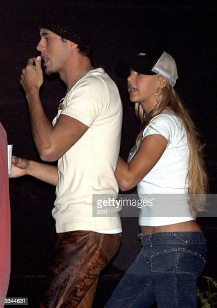 Spanish singer and musician Enrique Iglesias stands with his girlfriend Anna Kournikova on the backstage of a concert entitled 'The Seven Tour' at...