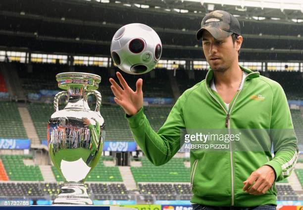 Spanish singer Enrique Iglesias plays with a ball next the Euro Trophy at Ernst Happel stadium in Vienna on June 27 2008 Enrique Iglesias will...