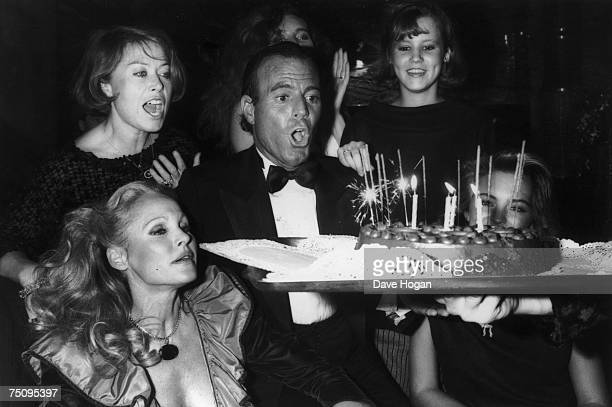 Spanish singer Julio Iglesias blows out the candles on his birthday cake 1983 Swiss actress Ursula Andress is among the guests