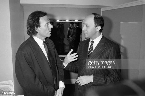 Spanish singer Julio Iglesias talks backstage with French Prime Minister Laurent Fabius after the charity concert given for the association SOSDrogue...