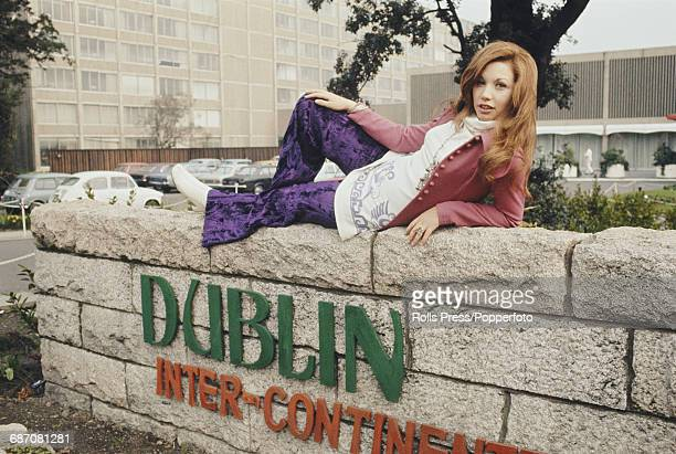 Spanish singer Karina posed wearing a pair of purple velvet loon pants as she lies on a wall in front of her hotel before going on to perform the...