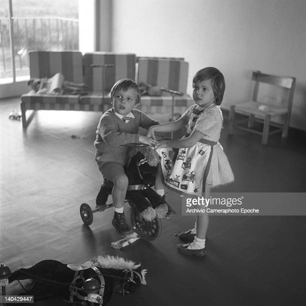 Spanish singer Miguel Bose riding a rocking horse and playing with a little girl Madrid 1960s