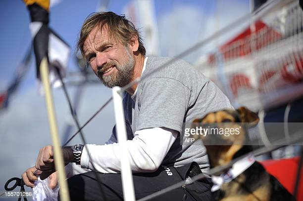 Spanish skipper Javier Sanso poses with his dog 'Botox' on board his monohull 'Acciona' on November 7 2012 in Les Sables d'Olonne western France a...