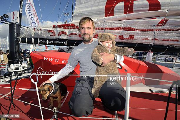 Spanish skipper Javier Sanso poses with his son Javier and his dog 'Botox' on board his monohull 'Acciona' on November 7 2012 in Les Sables d'Olonne...