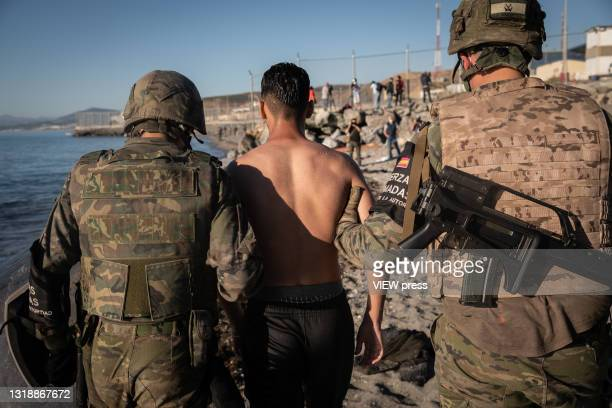 Spanish soldier accompanies a young migrant, who crossed the border between Spain and Morocco by swimming, to be return him to Morocco on May 19,...