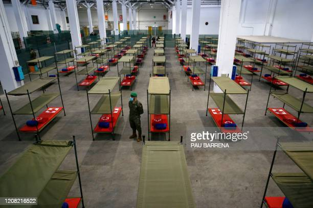 Spanish soldier stands next to beds set up at a temporary hospital for vulnerable people at the Fira Barcelona Montjuic centre in Barcelona on March...