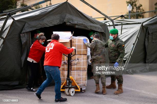 Spanish soldiers and Red Cross members gather equipment for a temporary hospital for vulnerable people set up at the Fira Barcelona Montjuic centre...