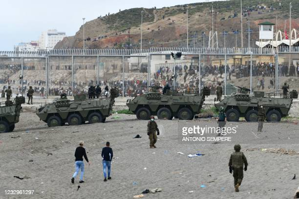 Spanish soldiers and Spanish Guardia Civil officers patrol after some 6,000 migrants entered the Spanish enclave of Ceuta as hundreds more tried to...