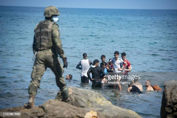 Spanish soldiers stand guard and intervene as migrants arrived swimming to Spanish territory of Ceuta on May 18, 2021. Starting on Monday, an...