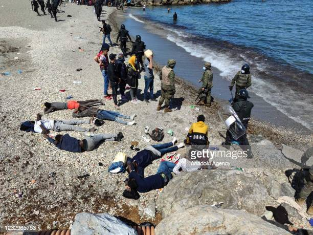 Spanish soldiers stand guard as migrants who arrived swimming to Spanish territory of Ceuta rest on May 18, 2021. Starting on Monday, an...
