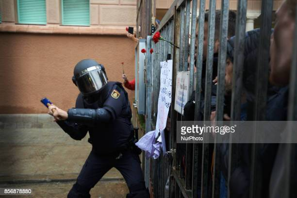 A Spanish State Police officer uses a malllet to break in the IES Pau Claris polling station as voters show carnations in sign of peace Spanish State...