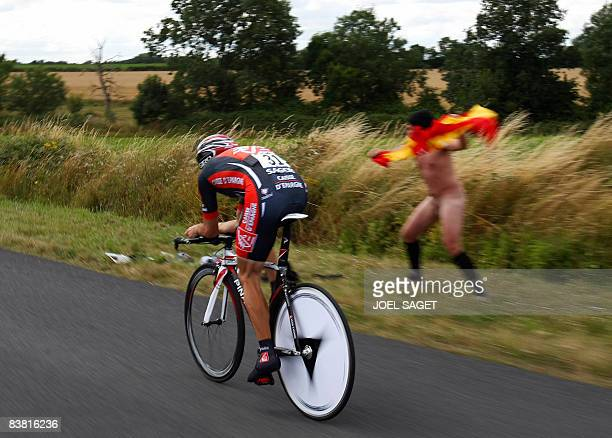 A Spanish streaker waves a Spanish flag as compatriot team leader Alejandro Valverde competes on July 8 2008 in the 29km individual timetrial and...