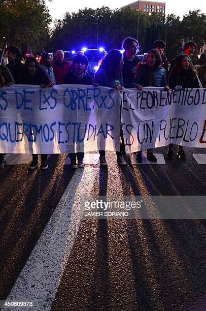 Spanish students protest during a demonstration in the streets of Madrid on November 20 2013 against cuts to education budgets and increases in fees...