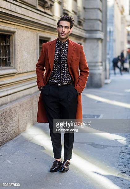 Spanish supermodel Jon Kortajarena wearing a dark orange peacoat printed tie and shirt and dark pleated trousers outside Salvatore Ferragamo during...