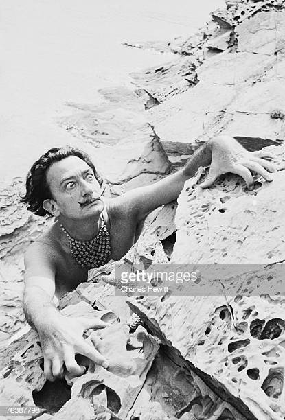 Spanish surrealist artist Salvador Dali clutches at the rock face at his home in Cadaques on the Costa Brava Spain 8th January 1955 Original...