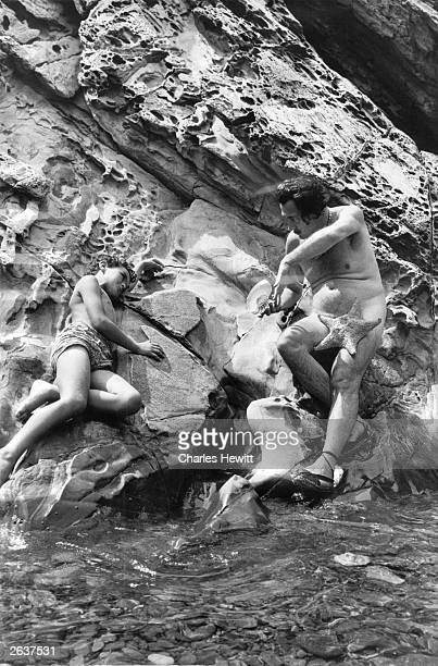 Spanish surrealist artist Salvador Dali his modesty protected only by a starfish talking with Juan Figeuras on the rocks near his home in Cadaques...