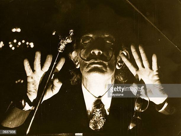 Spanish surrealist artist Salvador Dali in a mystical pose at the opening of his ChronoHologram exhibition