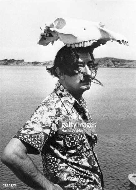 Spanish surrealist artist Salvador Dali wearing an animal skull as a hat