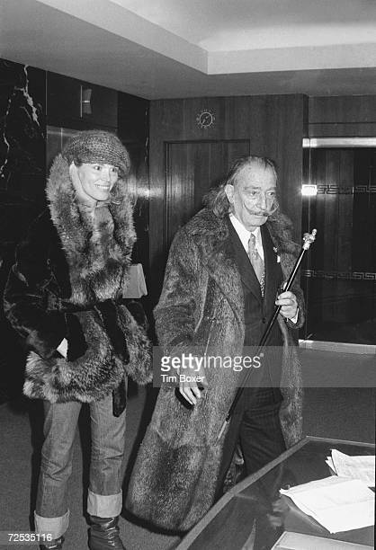 Spanish surrealist painter and artist Salvador Dali and Hong Kongborn French model and disco singer Amanda Lear wear fur coats as they walk in the...