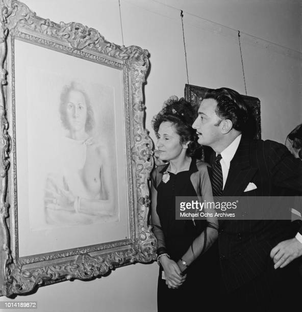 Spanish surrealist painter Salvador Dali and his wife Gala attend an exhibition of his works at the M Knoedler and Co gallery in New York City circa...