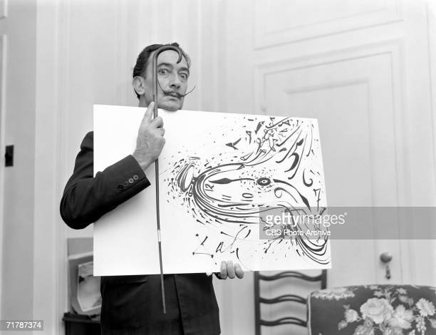 Spanish surrealist painter Salvador Dali holds up a painting and a cane for a broadcast of the CBS television program 'Person to Person' hosted by...