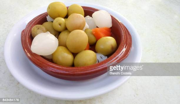 spanish tapa of green olives and onions marinated in olive oil - spanish olive stock photos and pictures