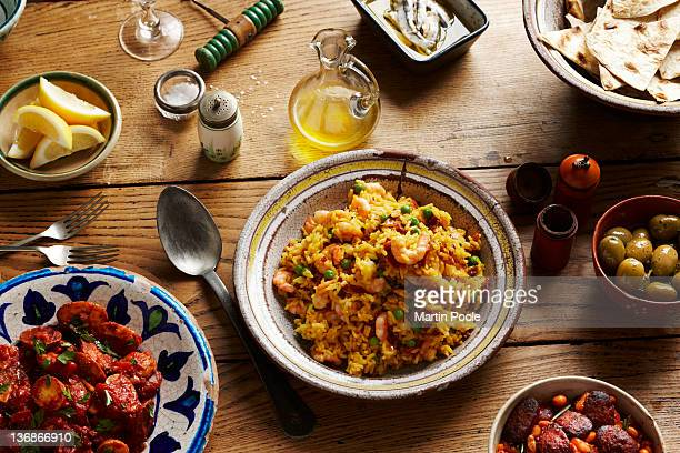 spanish tapas and paella on table - spanische kultur stock-fotos und bilder