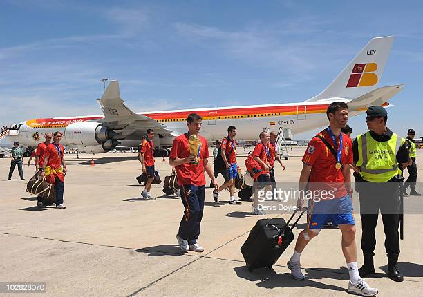 Spanish team captain Iker Casillas holds up the FIFA World Cup beside Xabi Alonso on their arrival at Barajas Airport on July 12 2010 in Madrid Spain