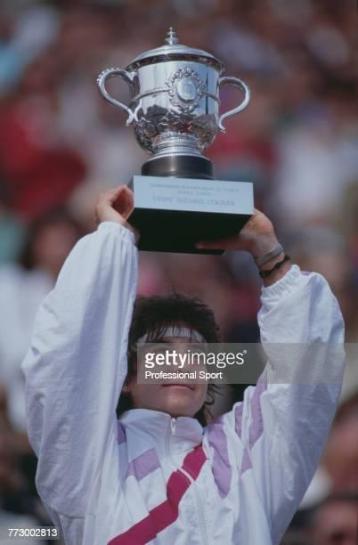 Spanish tennis player Arantxa Sanchez Vicario holds aloft the trophy after defeating German tennis player Steffi Graf 76 36 75 to win the Women's...