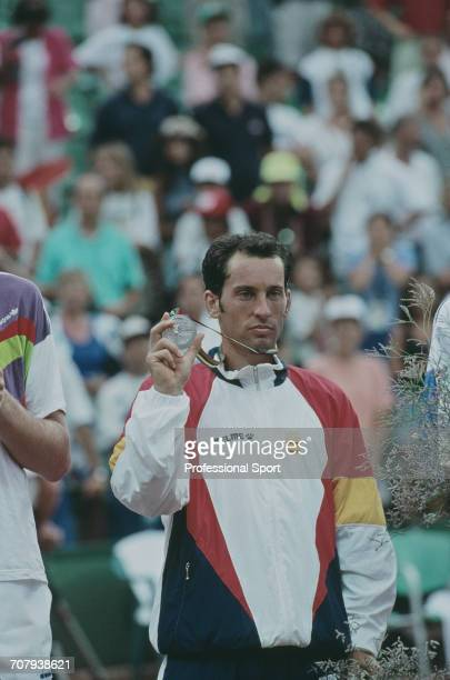 Spanish tennis player Jordi Arrese pictured holding up his silver medal on the medal podium after finishing in second place to Marc Rosset of...